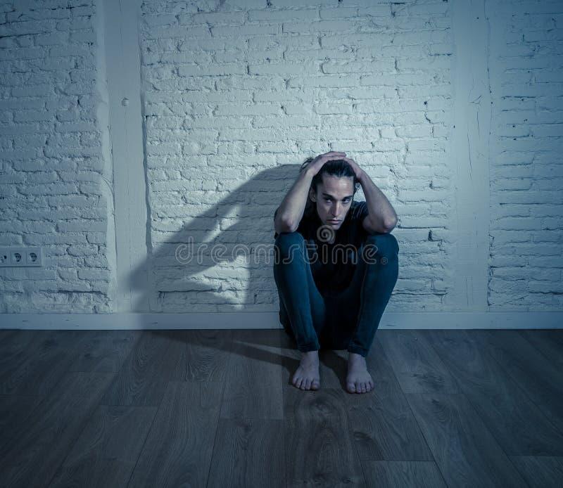 Uomo solo disperato dell'adolescente che soffre dalla depressione che si siede da solo sul pavimento a casa immagine stock
