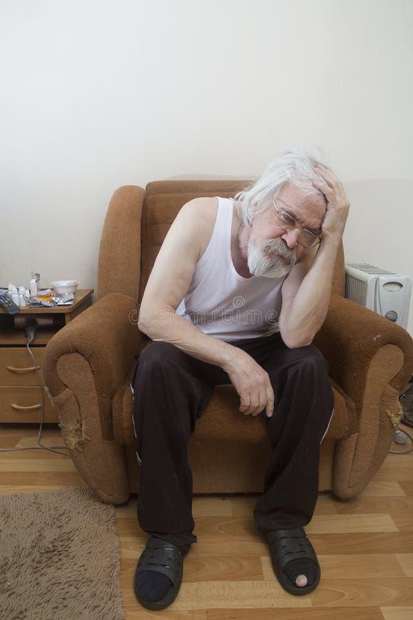 Uomo solo malato anziano nella poltrona a casa immagini stock libere da diritti