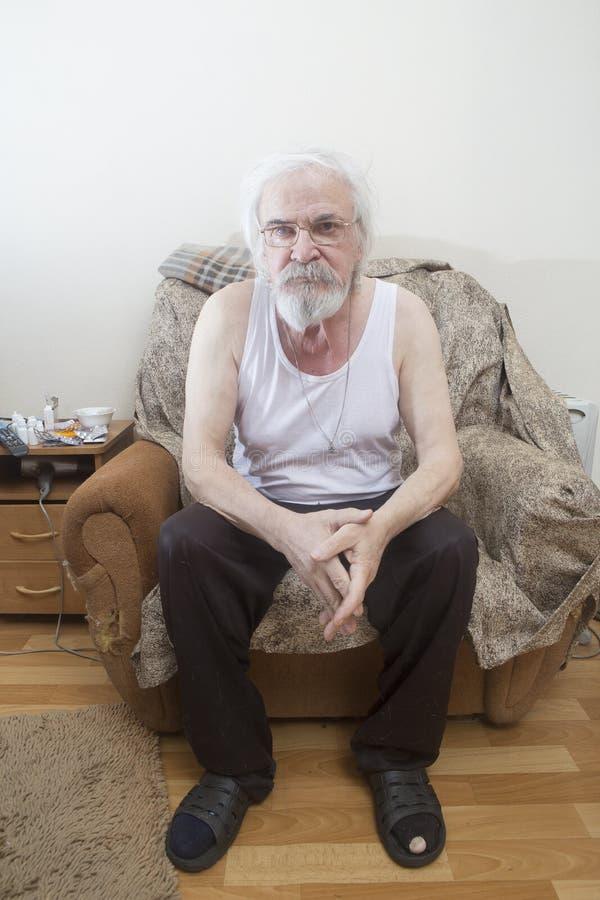 Uomo solo malato anziano nella poltrona a casa fotografia stock libera da diritti