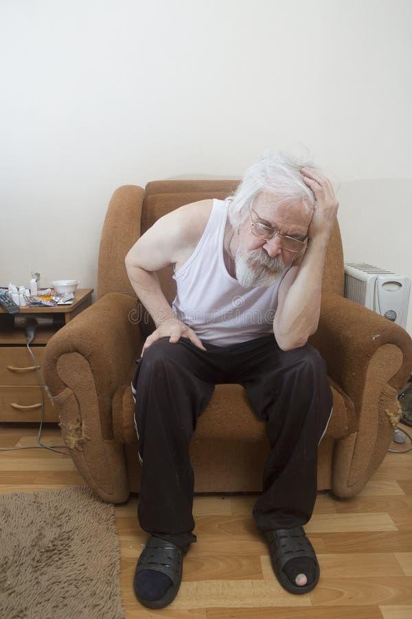 Uomo solo malato anziano nella poltrona a casa immagine stock
