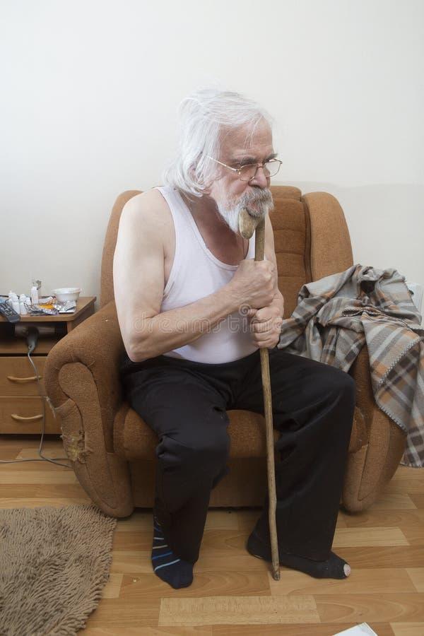 Uomo solo malato anziano nella poltrona a casa fotografia stock