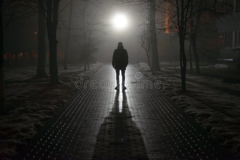 Uomo solo nella nebbia alla notte fotografie stock