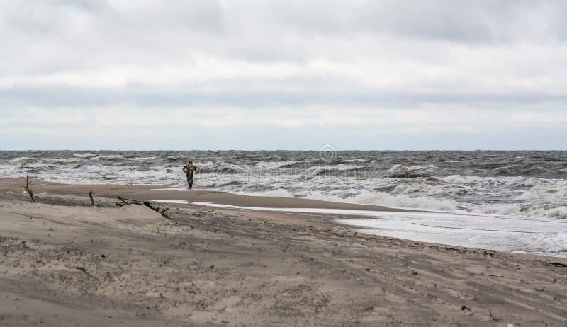 Uomo solo sulla spiaggia Riunione ambrata, tempo tempestoso fotografia stock libera da diritti