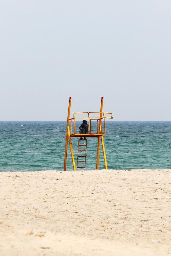 Uomo solo sulla torre arrugginita di salvataggio in mare fotografia stock libera da diritti