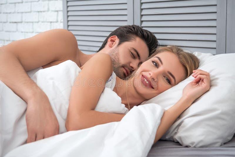 Uomo sonnolento che abbraccia donna nel letto fotografia stock libera da diritti