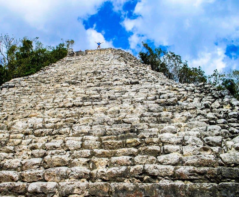 Uomo sopra la piramide maya a Coba nel Messico immagine stock libera da diritti