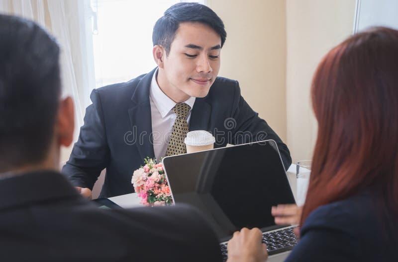 Uomo sornione di affari che esamina l'altro computer della gente fotografia stock