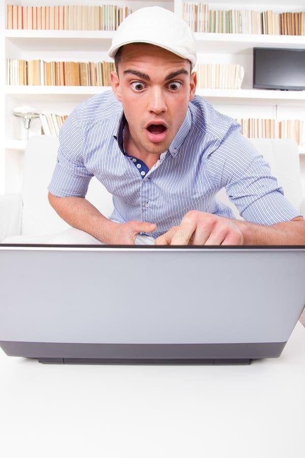 Uomo sorpreso che indica al monitor del computer con scossa fotografie stock