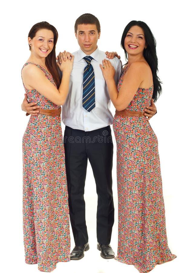 Uomo sorpreso che tiene due donne di risata fotografia stock