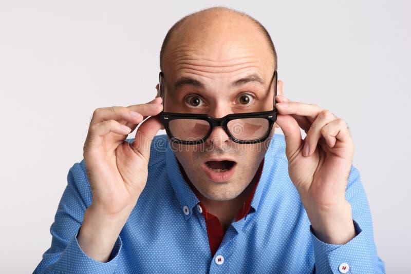 Uomo sorpreso in occhiali che esaminano macchina fotografica immagine stock libera da diritti