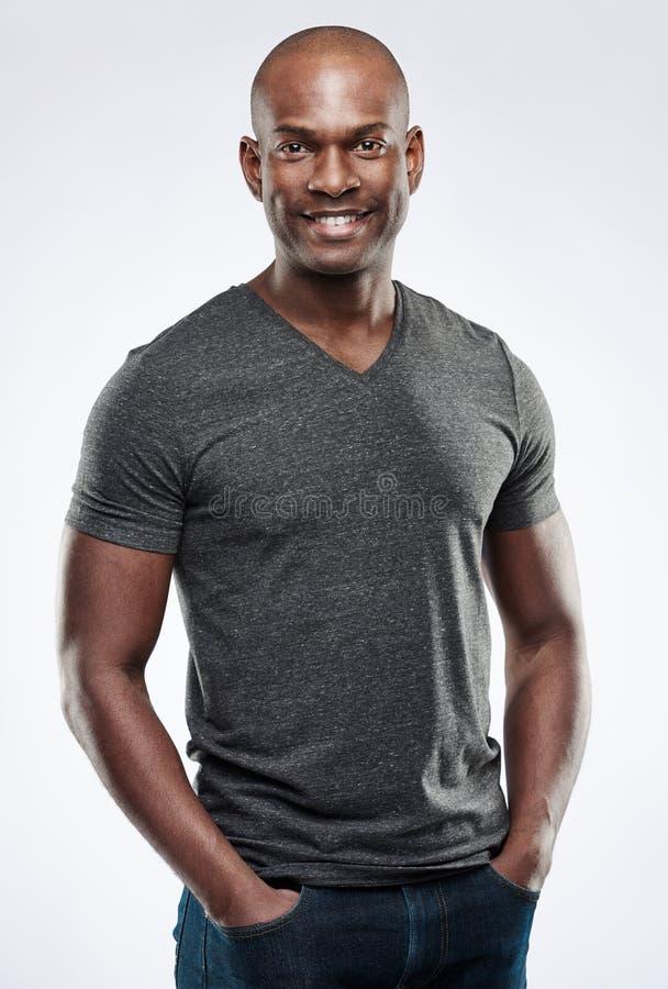 Uomo sorridente adatto bello con le mani in tasche fotografie stock libere da diritti