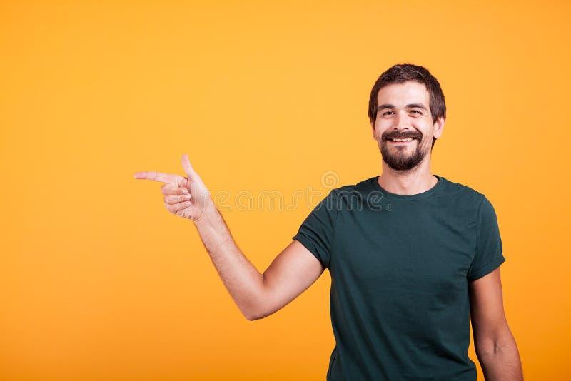 Uomo sorridente allegro che indica alla sua destra al copyspace immagine stock libera da diritti