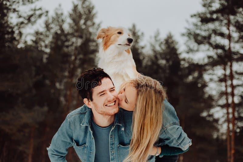 Uomo sorridente allegro felice con la ragazza ed il cane sul suo indietro baciare le coppie dei giovani nei vestiti del denim in  fotografia stock libera da diritti