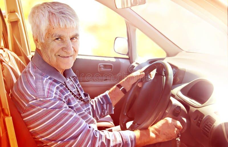 Uomo sorridente anziano alla ruota Giorno pieno di sole di autunno Rosso tonificato immagine stock libera da diritti