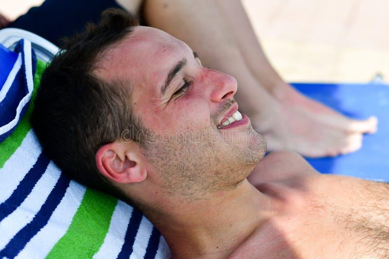 Uomo sorridente barbuto alla spiaggia fotografie stock libere da diritti