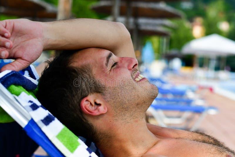 Uomo sorridente barbuto alla spiaggia immagine stock