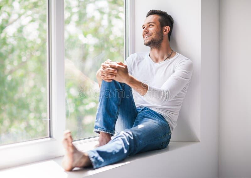Uomo sorridente bello che si rilassa sul davanzale della finestra fotografia stock