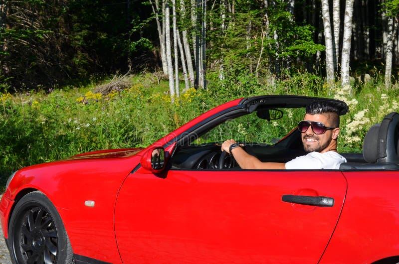 Uomo sorridente bello giovane in automobile lussuosa fotografia stock