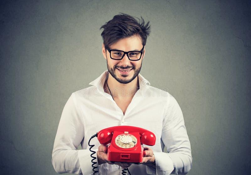 Uomo sorridente in camicia bianca e vetri che tengono telefono rosso che funziona per il servizio di assistenza al cliente fotografia stock libera da diritti