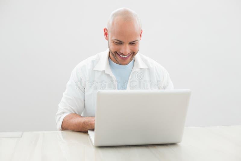 Uomo sorridente casuale che per mezzo del computer portatile allo scrittorio immagini stock libere da diritti