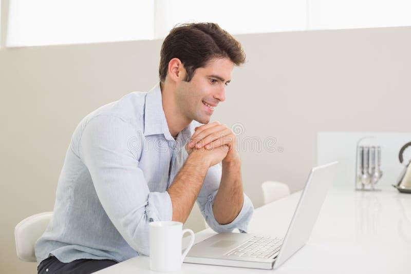 Uomo sorridente casuale che per mezzo del computer portatile a casa fotografia stock
