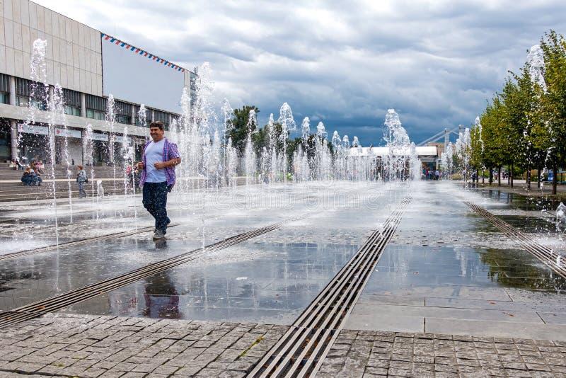 Uomo sorridente che cammina fra i getti della fontana fotografia stock libera da diritti