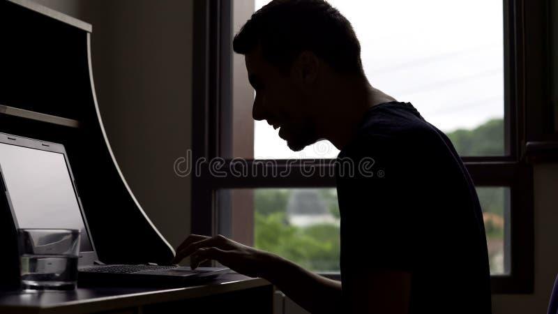 Uomo sorridente che chiacchiera con l'amico sul computer portatile, scherzoso e ridente, comunicazione fotografia stock