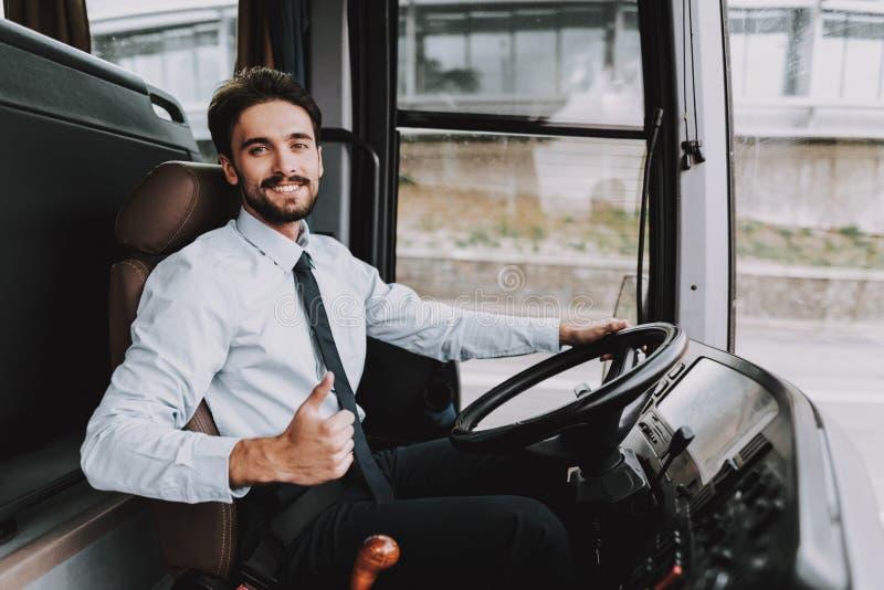 Uomo sorridente che conduce il bus di giro Driver professionale fotografia stock libera da diritti