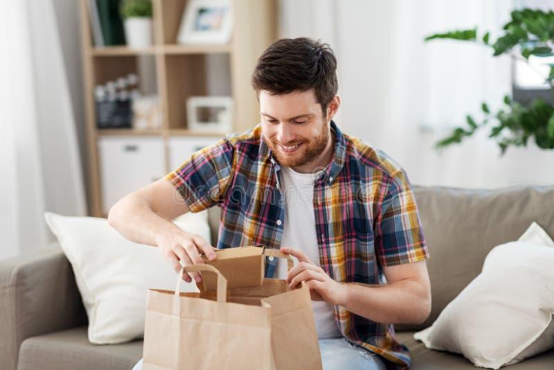 Uomo sorridente che disimballa alimento asportabile a casa fotografie stock