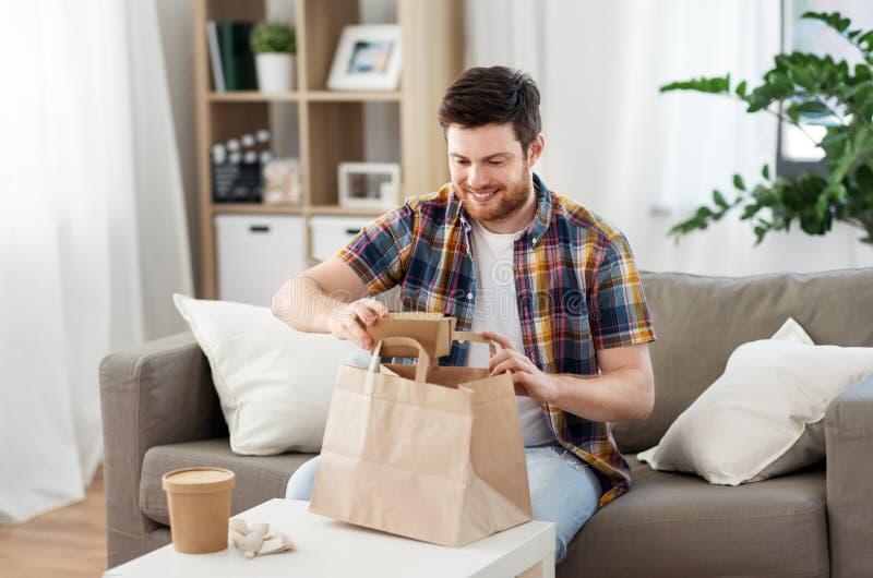 Uomo sorridente che disimballa alimento asportabile a casa fotografia stock