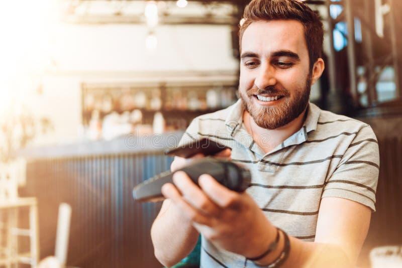 Uomo sorridente che effettua un pagamento senza fili, cliente che per mezzo del telefono cellulare, dispositivo con tecnologia de fotografia stock libera da diritti