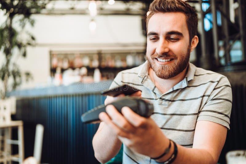 Uomo sorridente che effettua un pagamento senza fili, cliente che per mezzo del telefono cellulare, dispositivo con tecnologia de fotografia stock