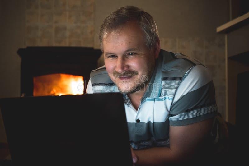 Uomo sorridente che guarda contenuto online su un computer portatile alla notte immagini stock libere da diritti