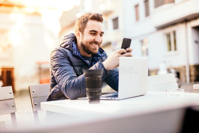 Uomo sorridente che lavora dall'ufficio all'aperto e dall'invio dei messaggi sullo smartphone nell'ambiente urbano immagine stock libera da diritti