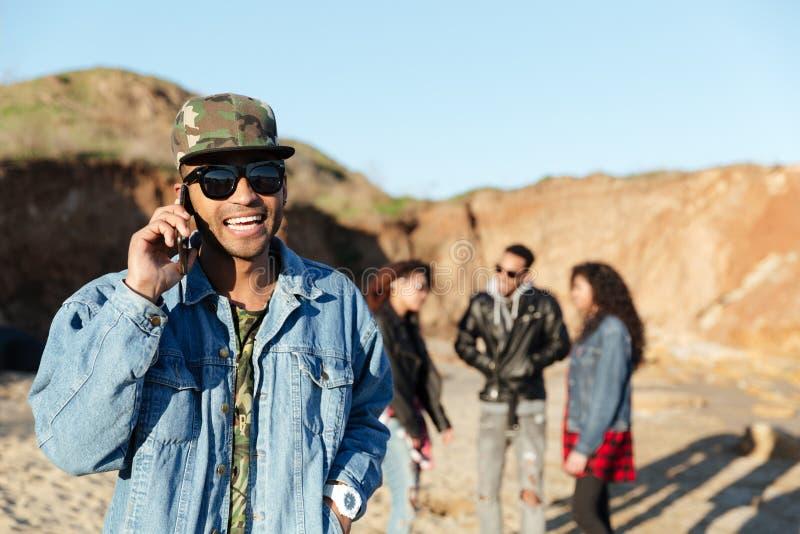 Uomo sorridente che parla dal telefono che cammina alla spiaggia con gli amici immagini stock libere da diritti