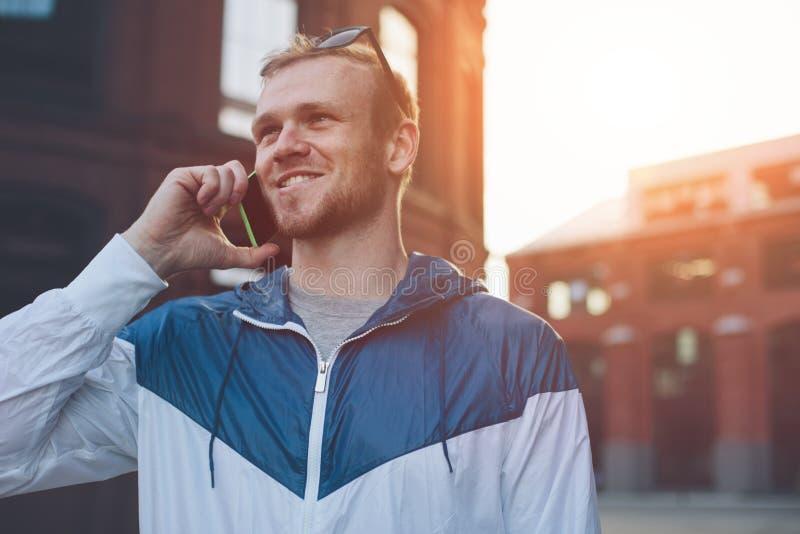 Uomo sorridente che parla sul telefono cellulare sulla via immagini stock