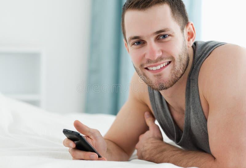 Uomo sorridente che per mezzo del suo telefono mobile fotografia stock