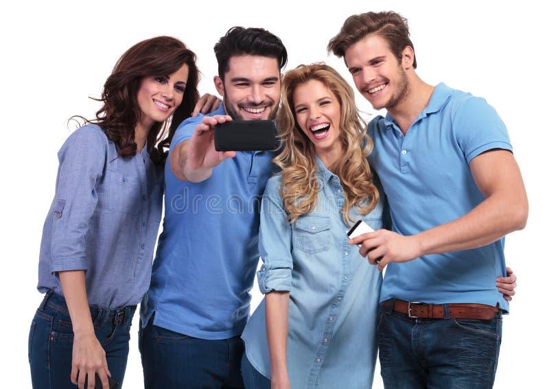 Uomo sorridente che prende una foto dei suoi amici con il telefono fotografie stock libere da diritti