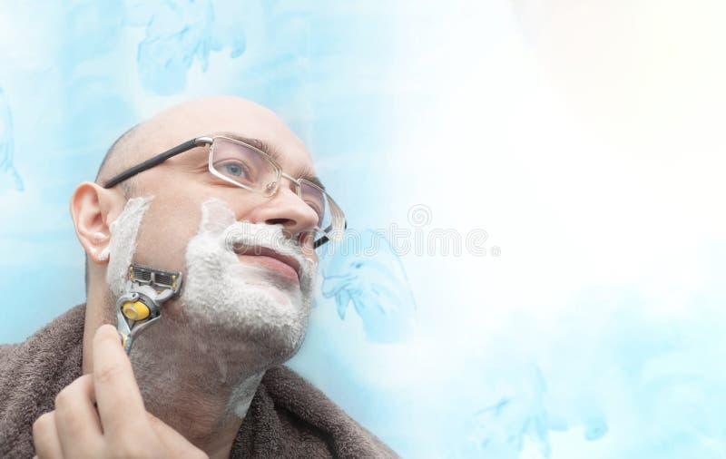 Uomo sorridente che rade la sua barba dalla lametta immagini stock