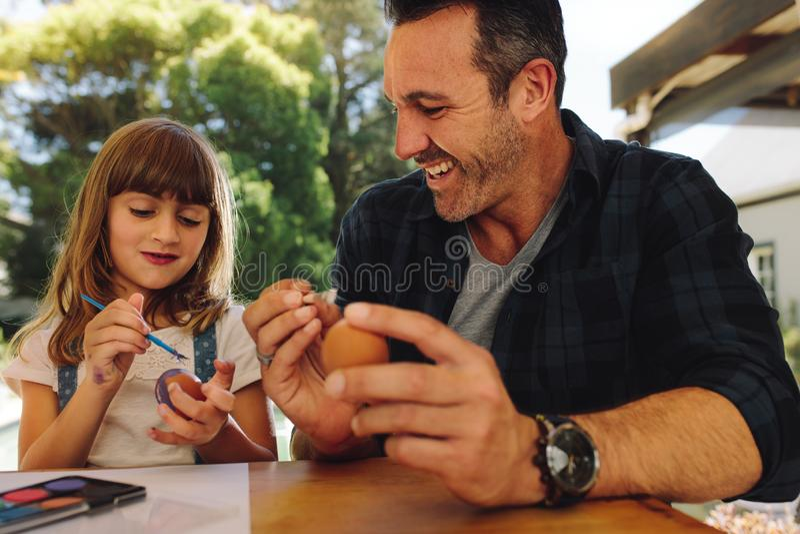 Uomo sorridente che si siede con le sue uova di Pasqua della pittura della figlia immagini stock