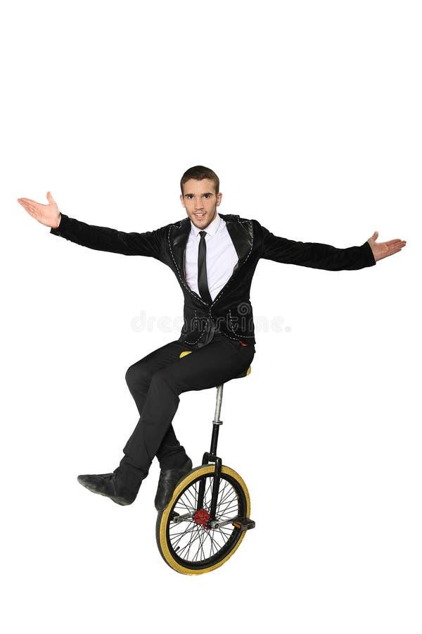 Uomo sorridente che si siede su un monociclo isolato immagini stock libere da diritti