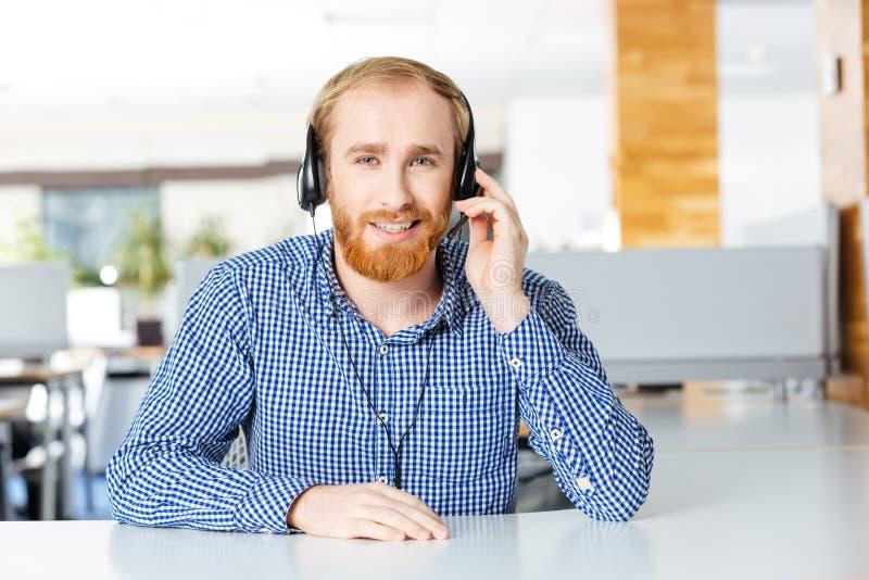 Uomo sorridente che si siede sul posto di lavoro e sul per mezzo della cuffia avricolare immagine stock