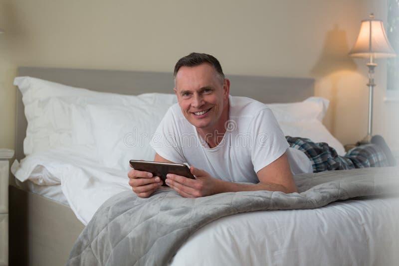 Uomo sorridente che si trova sul letto e sul utilizzare compressa digitale nella camera da letto fotografia stock libera da diritti