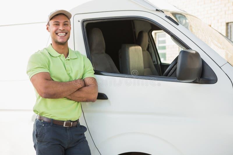 Uomo sorridente che sta contro il furgone di consegna fotografia stock