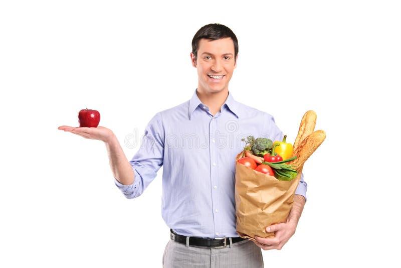 Uomo sorridente che tiene una mela rossa e un sacchetto immagine stock libera da diritti