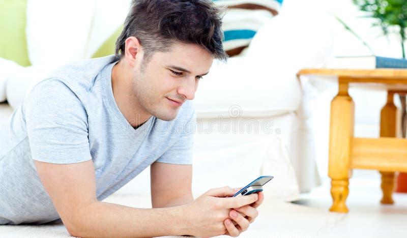 Uomo sorridente che trasmette un testo che si trova sul pavimento fotografia stock libera da diritti