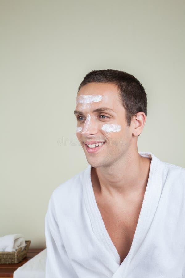 Uomo sorridente con crema sul suo fronte fotografia stock libera da diritti