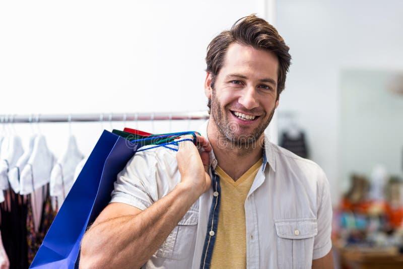 Uomo sorridente con i sacchetti di acquisto fotografie stock