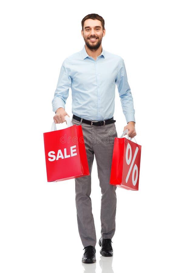 Uomo sorridente con il sacchetto della spesa rosso immagine stock libera da diritti