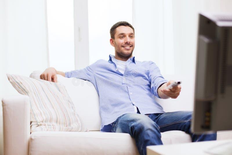 Uomo sorridente con il telecomando della TV a casa fotografia stock